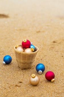 Weihnachtskugeln in einem korb am sandigen ufer des ozeans