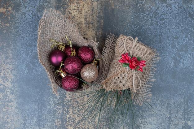 Weihnachtskugeln in sackleinen auf marmorhintergrund. hochwertiges foto
