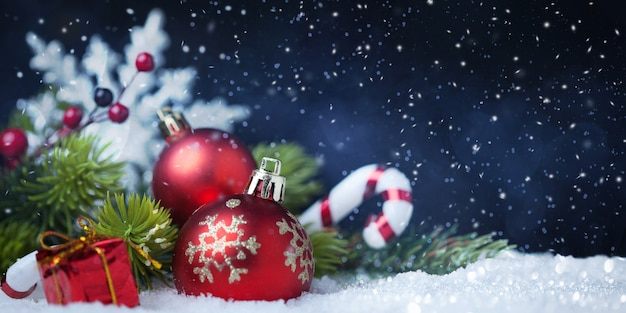 Weihnachtskugeln mit baum und dekorationen auf schnee