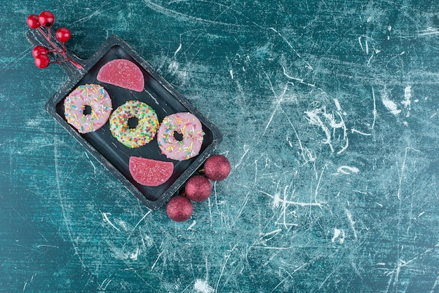Weihnachtskugeln neben donuts und marmeladen auf einer kleinen platte auf blau.