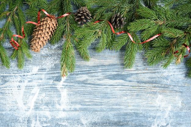 Weihnachtskugeln, tannenzweige, zapfen, schleife auf holzoberfläche. weihnachtsdekoration, kopierraum