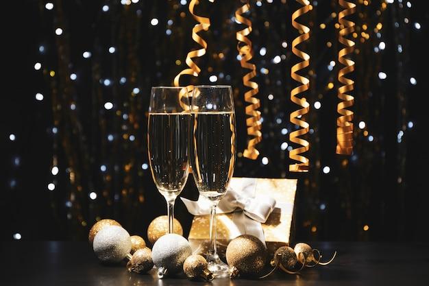 Weihnachtskugeln und champagnergläser auf verschwommenem raum, kopierraum