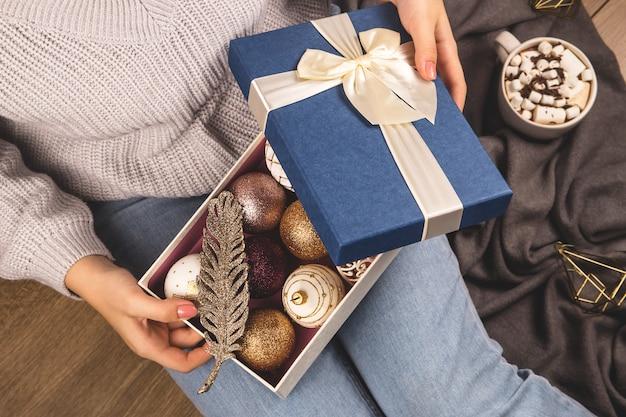 Weihnachtskugeln und dekor in einem kasten in den händen einer frau, die auf dem fußboden sitzt.