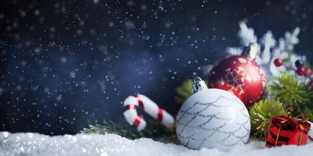 Weihnachtskugeln und dekoration auf dunkelblau mit schnee