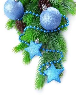 Weihnachtskugeln und dekorative sterne auf tannenbaum, lokalisiert auf weiß