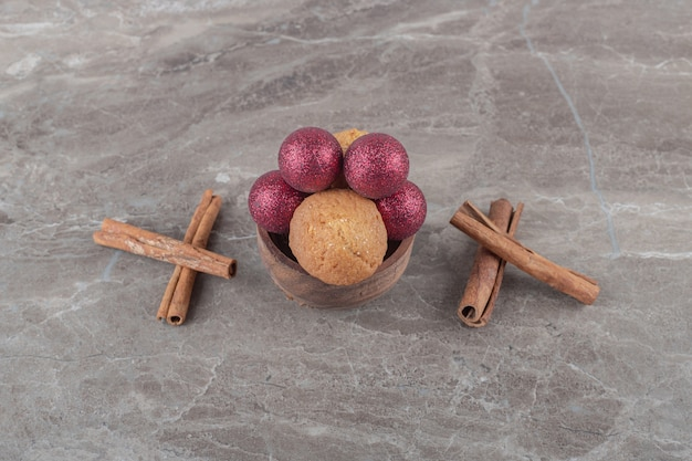 Weihnachtskugeln und ein keks in einer schüssel neben zimtstangen auf marmoroberfläche