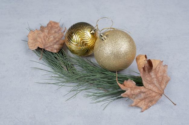 Weihnachtskugeln und getrocknete blätter auf grauem hintergrund. hochwertiges foto