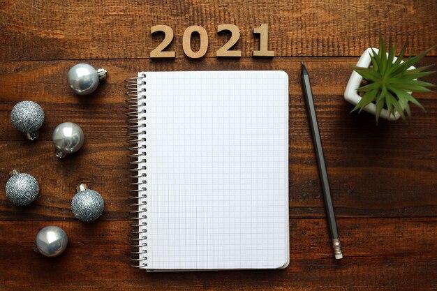 Weihnachtskugeln und leeres notizbuch zum schreiben von zielen
