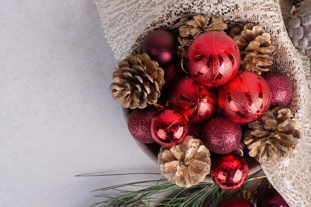 Weihnachtskugeln und tannenzapfen auf weißem tisch.