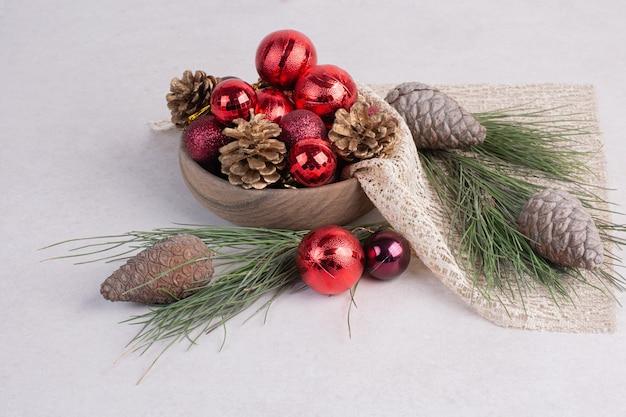 Weihnachtskugeln und tannenzapfen auf weißer oberfläche