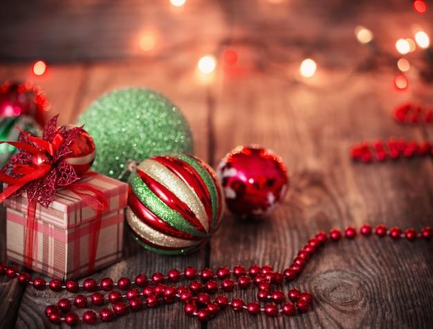 Weihnachtskugeln und weihnachtsgeschenk auf hölzernem hintergrund
