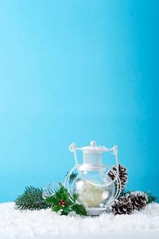 Weihnachtslaterne auf schnee mit tannenzweig und winterdekoration auf blau. feiertags-weihnachtskonzept.