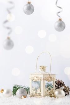 Weihnachtslaterne auf schnee mit tannenzweig und winterdekoration auf weiß. feiertags-weihnachtskonzept.
