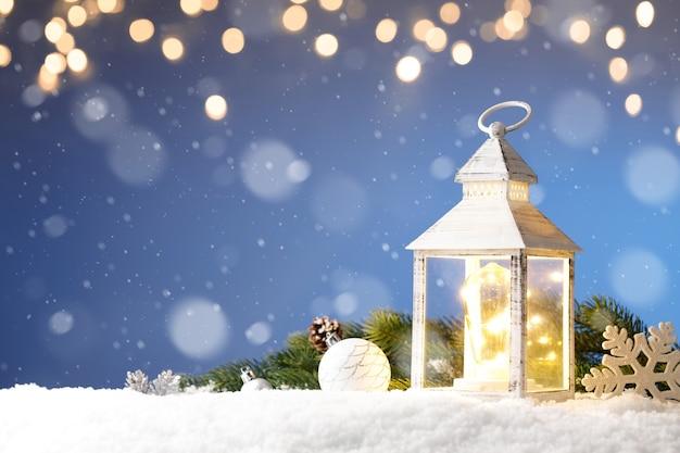 Weihnachtslaterne im schnee mit kerzenlicht
