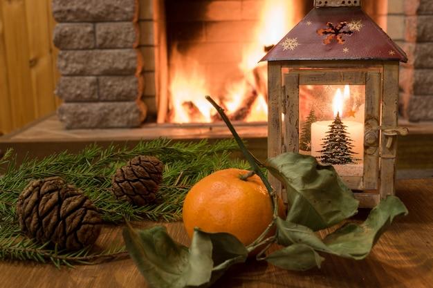 Weihnachtslaterne, kerzen und zapfen auf altem braunem tisch, vor gemütlichem kamin.