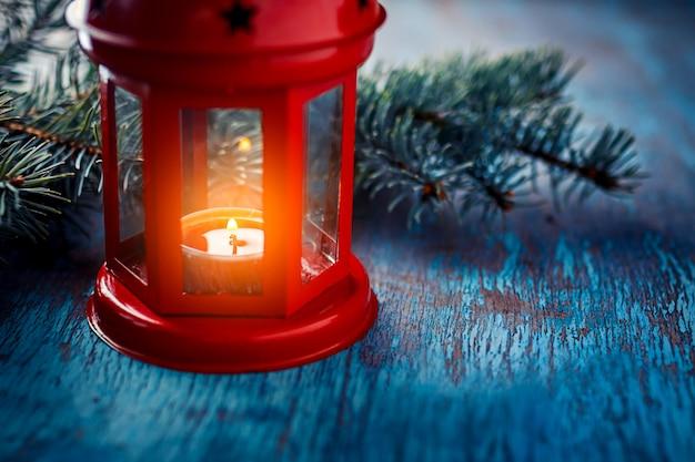 Weihnachtslaterne mit einer kerze und einer niederlassung eines weihnachtsbaums