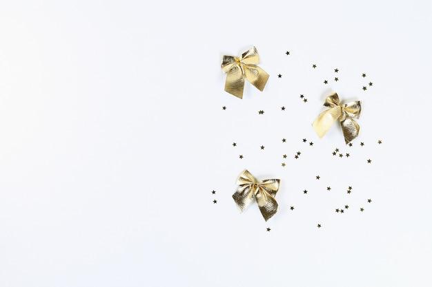 Weihnachtslayout. goldene konfetti in form von sternen und bögen auf einem weißen hintergrund.