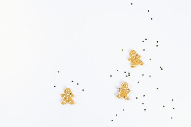 Weihnachtslayout. goldene sternförmige konfetti und selbst gemachte ingwerplätzchen auf einem weißen hintergrund.