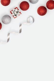 Weihnachtslayout mit leuchtend roten und silbernen weihnachtskugeln und kleiner geschenkbox oder geschenk auf weiß