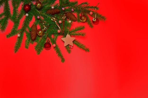 Weihnachtslayout roter serviettenbaumzweig mit weihnachtsspielzeug auf rotem hintergrund