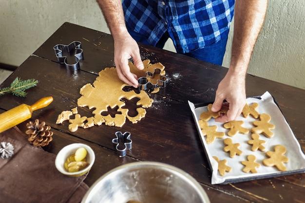 Weihnachtslebensmittel mann, der lebkuchenplätzchenausgangsküche weihnachtsnachtisch kocht