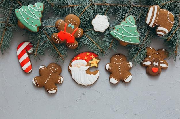 Weihnachtslebkuchen auf einem grauen hintergrund mit kiefernbrunchs.