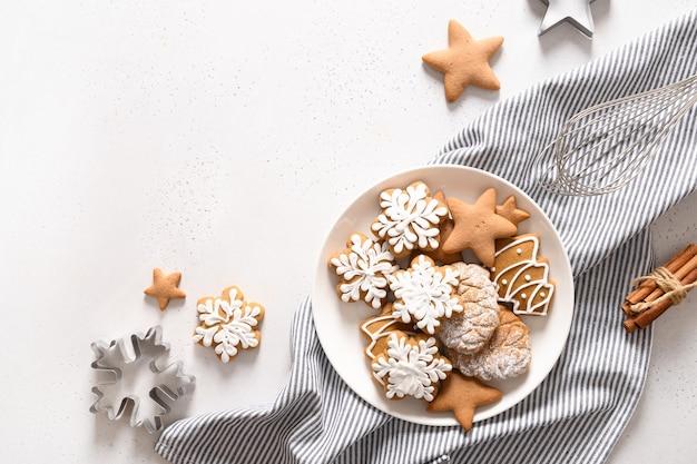 Weihnachtslebkuchen glasierte kekse in platte auf weißem hintergrund. von oben betrachten. flach liegen.