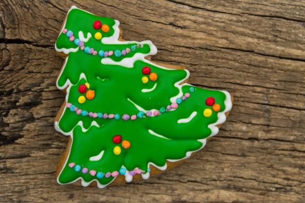 Weihnachtslebkuchen in form eines weihnachtsbaumes auf rustikalem holztisch