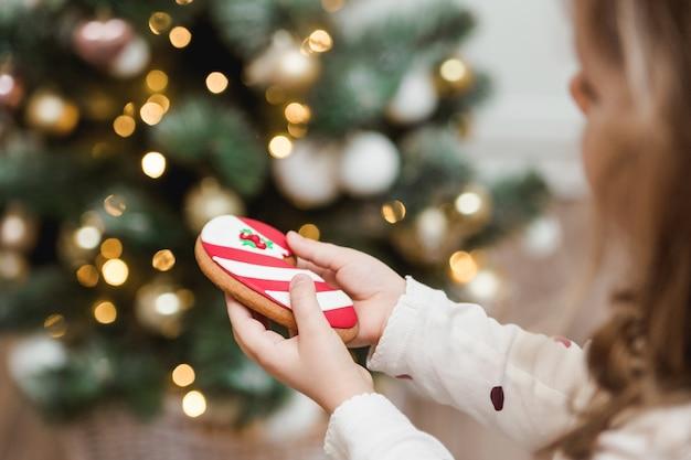 Weihnachtslebkuchen in kinderhänden. weihnachtsbaum mit hellem hintergrund.