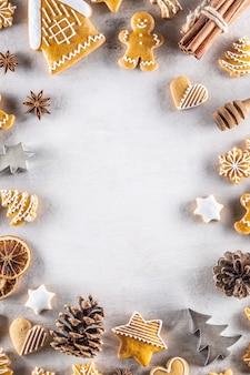 Weihnachtslebkuchen liegen zusammen mit zimt und tannenzapfen auf dem tisch - kopierraum.