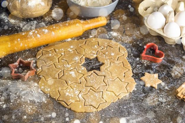 Weihnachtslebkuchen mit zutaten auf dunklem hintergrund kochen. getöntes bokeh und schnee