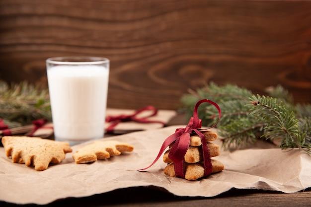 Weihnachtslebkuchen und ein glas milch auf dunklem holzbrett.