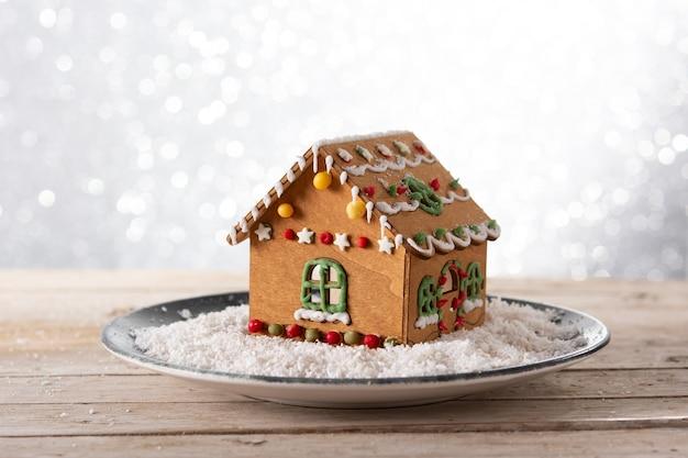 Weihnachtslebkuchenhaus auf glitzerhintergrund