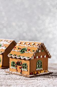 Weihnachtslebkuchenhaus auf weißem glitzerhintergrund