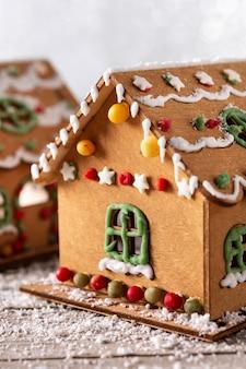 Weihnachtslebkuchenhaus verziert mit bonbons und glasur auf holztisch