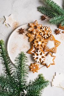 Weihnachtslebkuchenhintergrundplätzchen mit tanne, kiefer, auf weißer beschaffenheit frohes neues jahr feiertagskonzept, vertikal