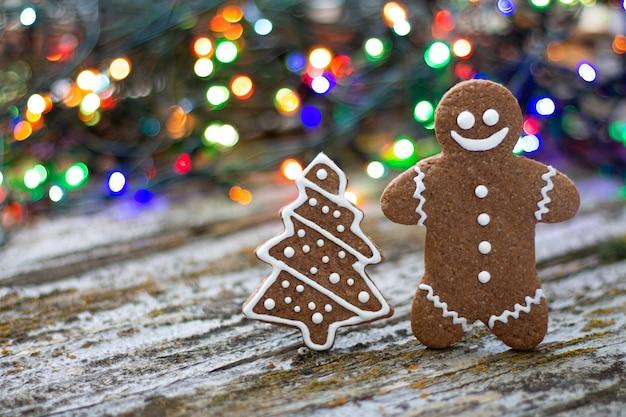 Weihnachtslebkuchenmann und -baum auf rustikalem hintergrund mit buntem bokeh