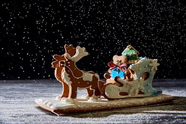 Weihnachtslebkuchenpferdeschlitten mit rotwild auf einer dunkelheit mit fallendem schnee.