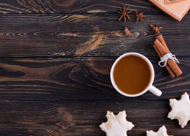 Weihnachtslebkuchenplätzchen auf einem hölzernen hintergrund mit aromatischem kaffee und zimtstangen