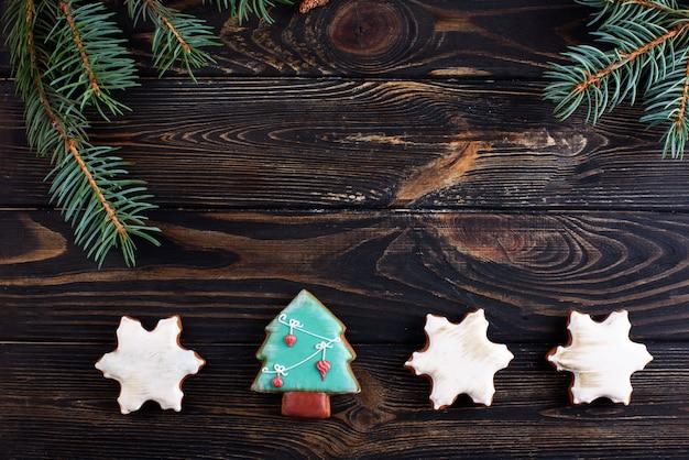 Weihnachtslebkuchenplätzchen auf einem hölzernen hintergrund mit einem zweig der fichte