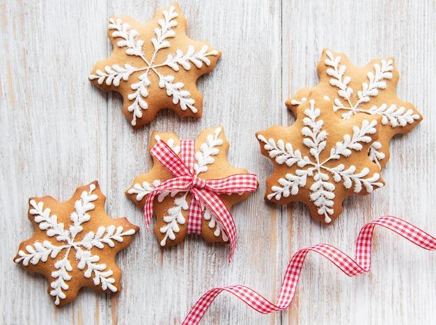 Weihnachtslebkuchenplätzchen auf einem weißen hölzernen hintergrund