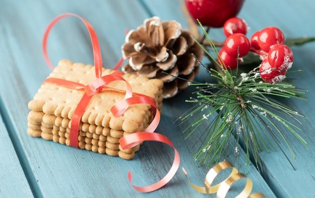 Weihnachtslebkuchenplätzchen auf weinleseplatte und anis, zimt, tannenzapfen, zedernzweige mit goldenen lichtern auf rustikalem tisch. gebackener traditioneller lebkuchenmann, baum, sternplätzchen