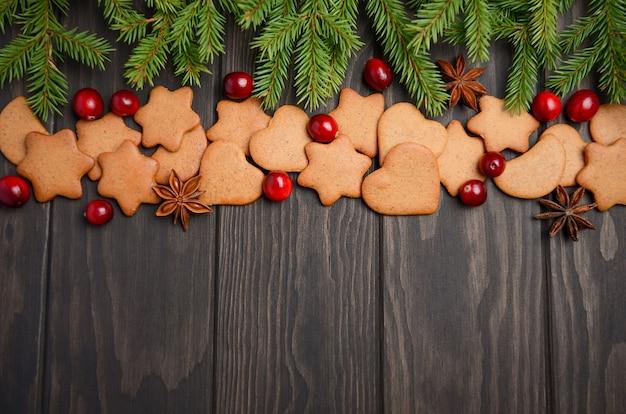 Weihnachtslebkuchenplätzchen. feiertagskonzept verziert mit tannenzweigen und moosbeeren