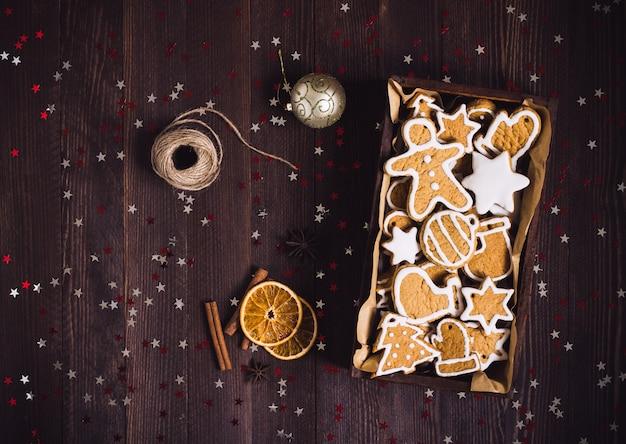 Weihnachtslebkuchenplätzchen im dunklen foto der draufsicht des festlichen gebäcks des holzkistegeschenks