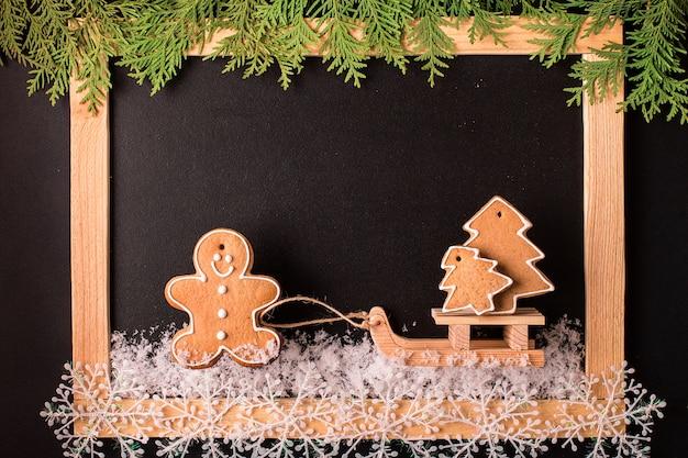 Weihnachtslebkuchenplätzchen mit leerer schwarzer tafel