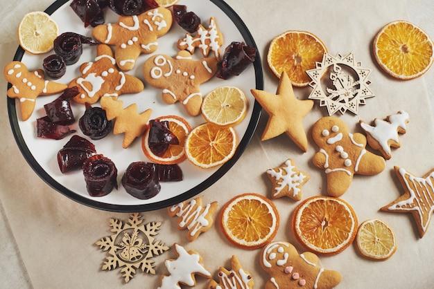 Weihnachtslebkuchenplätzchen und getrocknete orange und gewürze auf weißer tabelle. pastell, marmelade in rollen auf einem teller