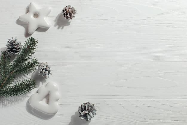 Weihnachtslebkuchenplätzchen und kiefernniederlassungen und -kegel auf einem weiß, copyspace.
