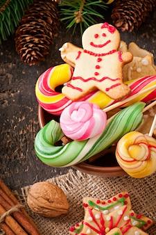 Weihnachtslebkuchenplätzchen und -lutscher auf altem hölzernem hintergrund