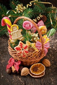 Weihnachtslebkuchenplätzchen und -lutscher in einem korb auf altem hölzernem hintergrund