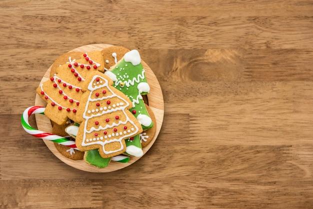 Weihnachtslebkuchenplätzchen und zuckerstange auf hölzernem hintergrund
